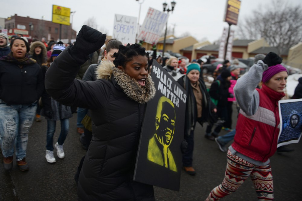Demonstrator Makela Roberts marches down University Ave. SE with fellow protestors during Monday's march in St. Paul. Roberts said she was