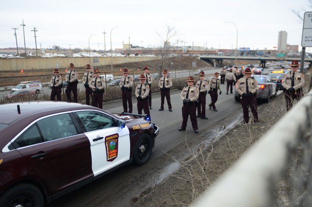 Minnesota State Police Troopers prevent a large group of demonstrators from entering I-94 during Monday's march in St. Paul.