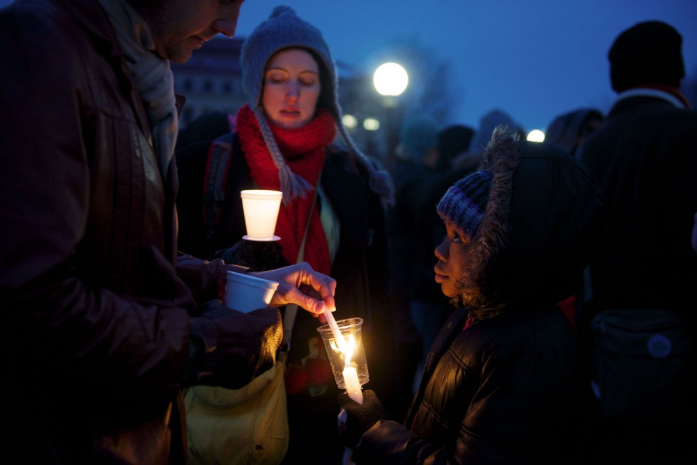 Khilanni Easterling helps ignite the candles of demonstrators in front of the capitol on Monday evening.
