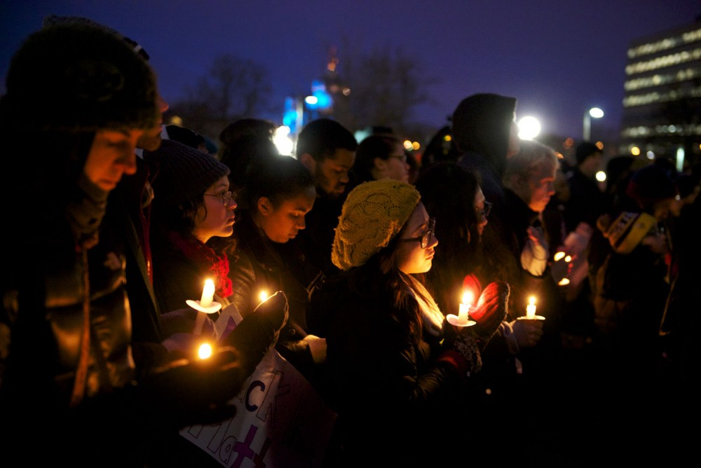 Demonstrators stand, holding candles in front of the state capitol on Monday evening.