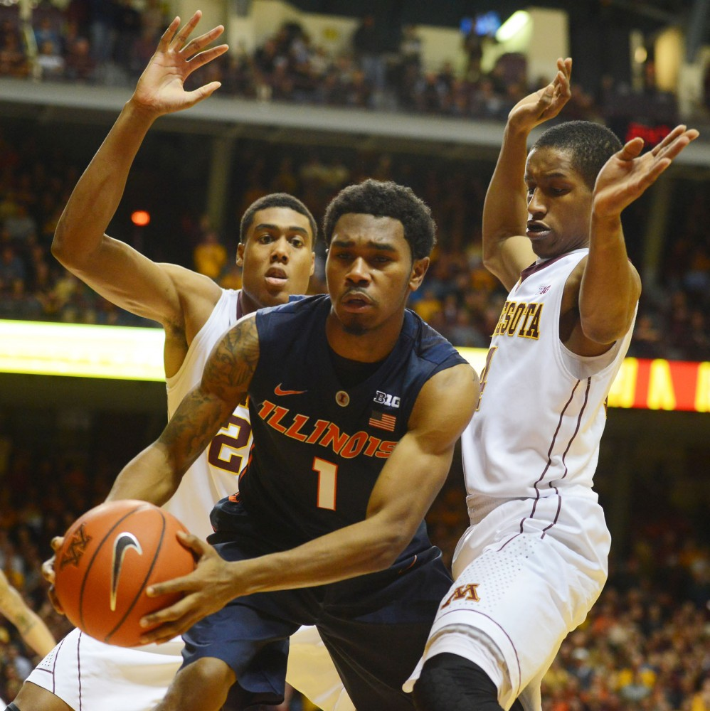 Illinois guard Jaylon Tate fights against defense by guard DeAndre Mathieu and forward Charles Buggs on Saturday at Williams Arena.