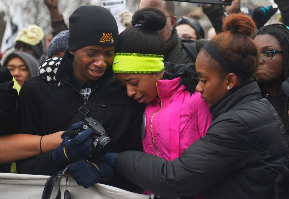 Lafayette Doty, Alex Doty and Jade Greear, relatives of Marcus Golden, become emotional outside the Capitol on Monday. Estimated 2,000 people joined the MLK march from Snelling and University to the Capitol.