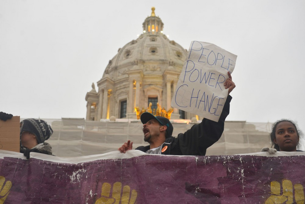 Gilbert Rodriquez chants with other demonstrators after the MLK march comes to an end outside the Capitol on Monday.