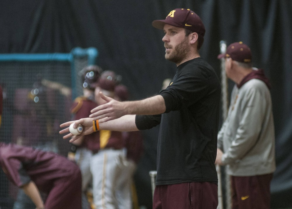 Interim pitching coach Scott Matyas speaks to players during practice at Bierman Field Athletic Building on Tuesday afternoon. Matyas pitched for the Gophers from 2008-2011 and is currently filling in for Todd Oakes.