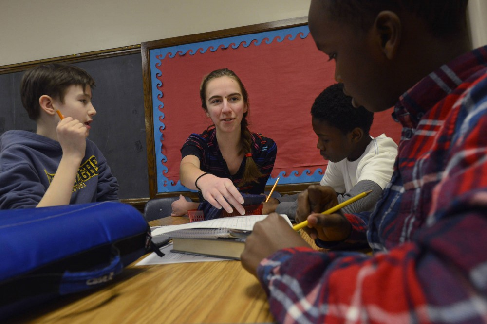 Freshman volunteer Leyla Soyak works with students on math problems at Ramsey Middle School in Minneapolis on Tuesday.