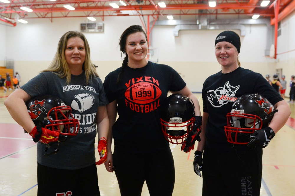 University student Nikki Graf stands in between alumnae Laura Brown (left) and Nikki Beyer at their practice in Bloomington on Saturday. Their team, the Minnesota Vixen, are the longest continuously operating womens football team in the nation.
