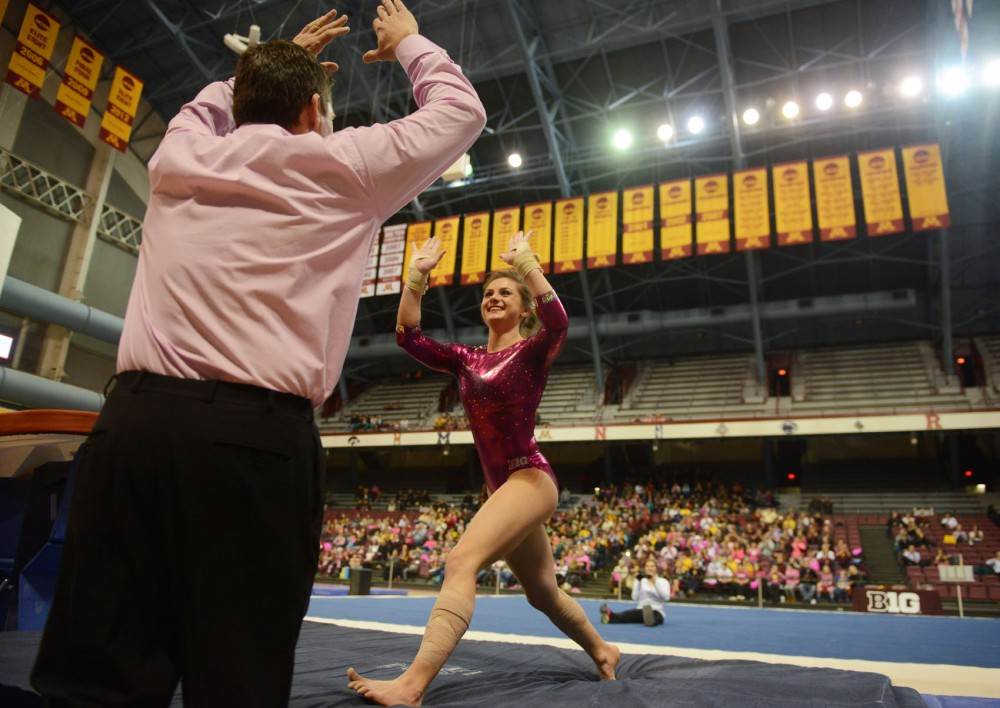 Sophomore Rachel Haines celebrates with assistant coach Rich Stenger after her vault performance at the Sports Pavilion on Saturday evening against Nebraska.