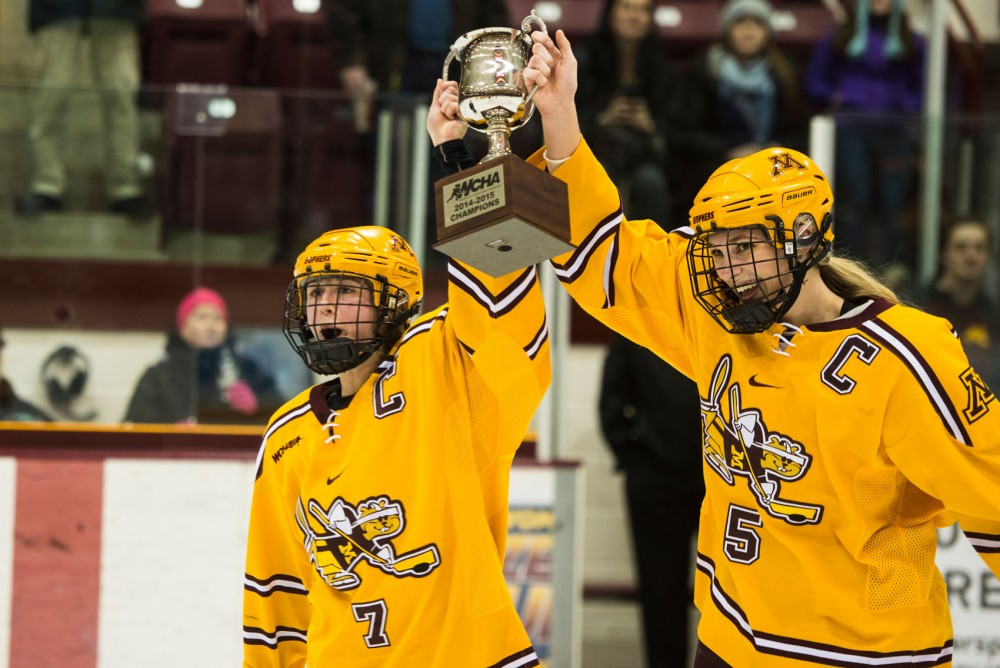 Senior captains Rachael Bona and Rachel Ramsey hold the WCHA trophy after defeating the Minnesota-Duluth Bulldogs 2-0 on Saturday evening at Ridder Arena.