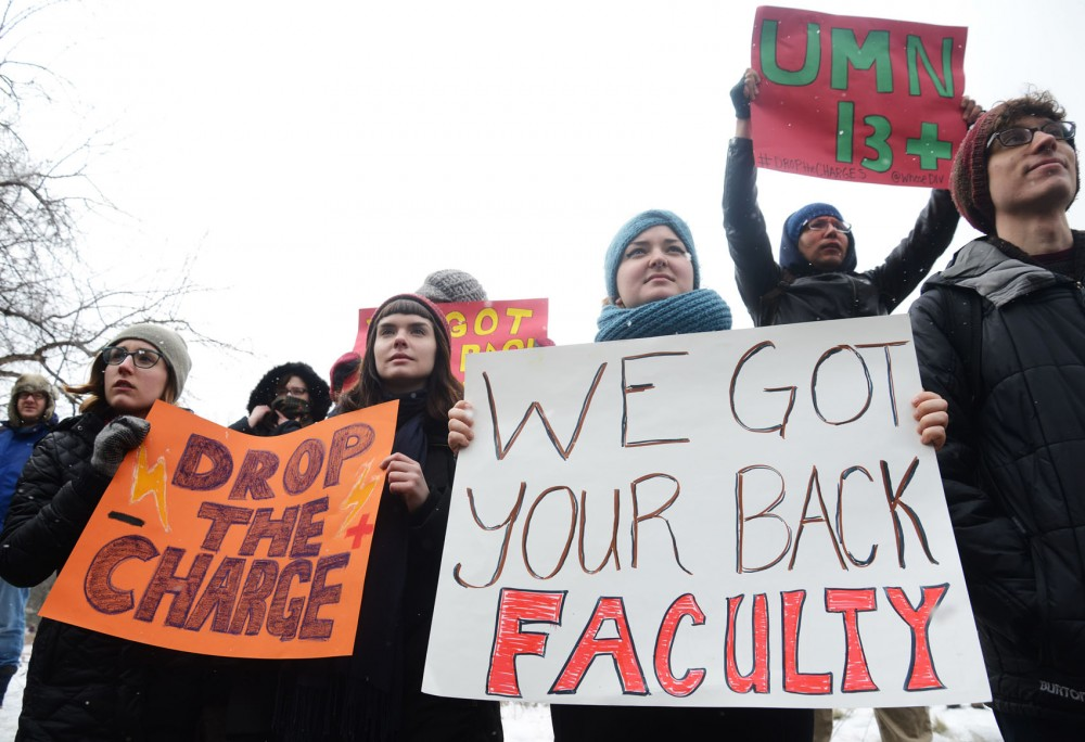 Students and faculty members hold signs at a protest outside Morrill Hall on Monday. Demonstrators protested the arrest of 13 students who occupied President Eric Kaler's office last week.