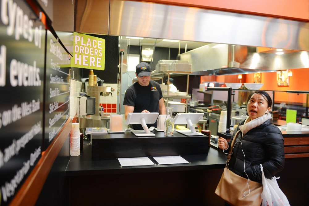 St. Paul resident Mollie Thao browses the menu at the new Afro Deli location in downtown St. Paul on Tuesday evening. Afro Deli started five years ago in Cedar-Riverside via a partnership with the African Development Center.