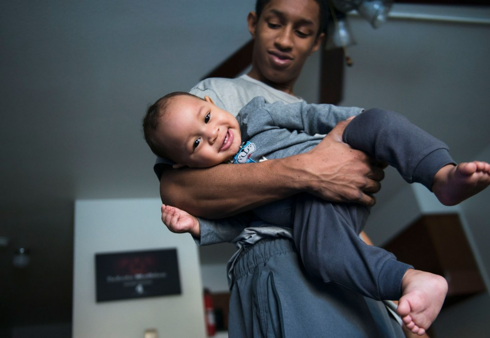 Gophers point guard DeAndre Mathieu cradles his 7-month-old son, Elijah, at his apartment on Sunday.