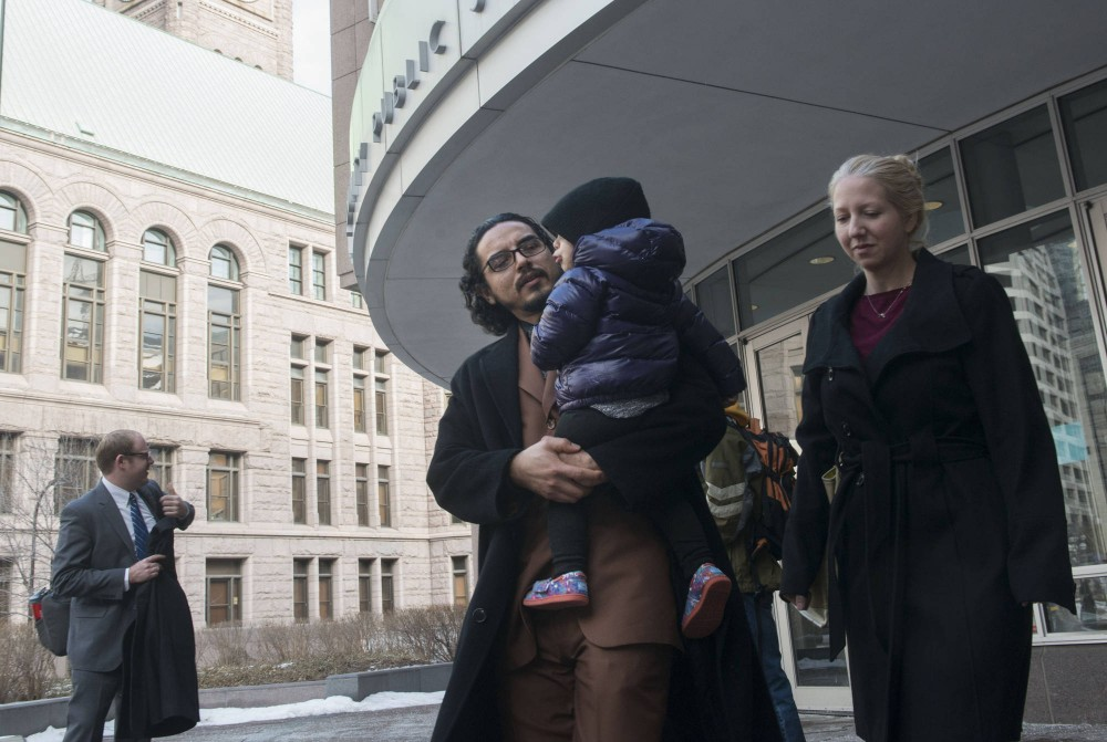 Whose Diversity? member David Melendez holds his daughter as he leaves the Hennepin County Public Safety Facility after a court appearance on Tuesday morning.