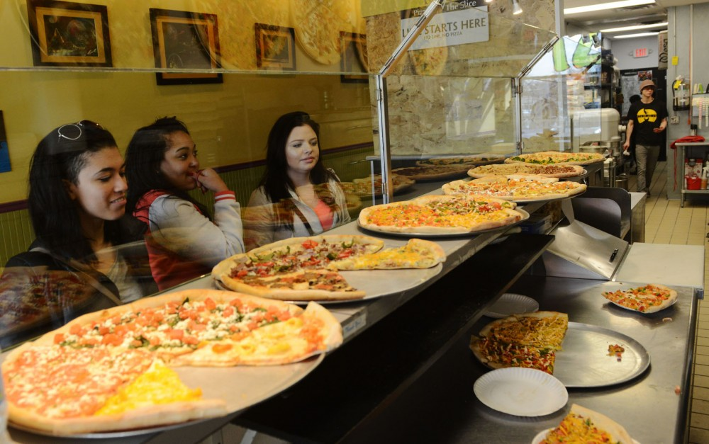 Morgan Lambert, Geena Funk and Erin Marie pick out slices on Wednesday at Mesa Pizza in Uptown. Mesa expanded its business from Dinkytown to Uptown in 2011.