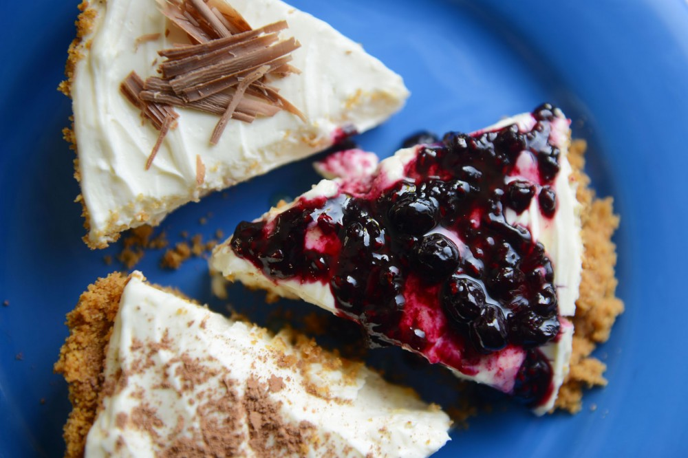 A variety of no-bake cheese cakes slices, topped with berries, cocoa and chocolate shavings.
