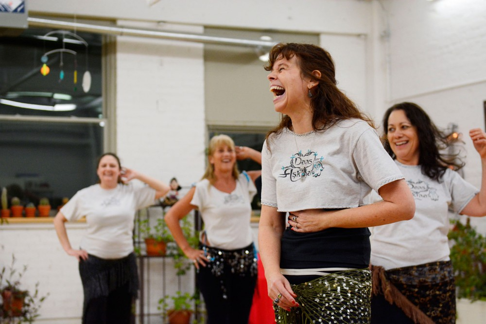 Dans Askina founder and instructor Amina Beres shares a laugh with team members during rehearsal on January 29.