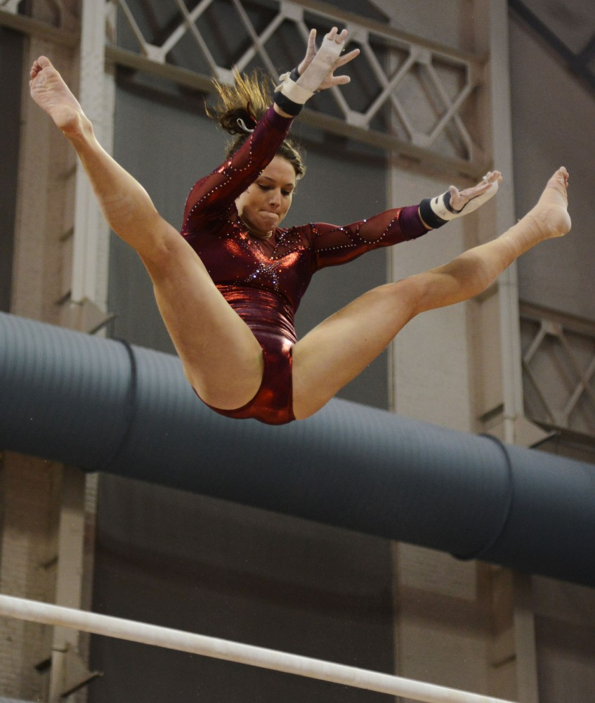Senior Cierra Tomson performs on the bars on Saturday evening at the Sports Pavillon against New Hampshire and Iowa.