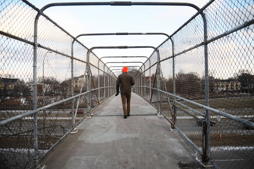 A pedestrian walks over 5th Avenue bridge on Sunday. Marcy-Holmes sent a letter Thursday to MnDOT's transportation commissioner asking for a new bridge to connect 5th Street Southeast.