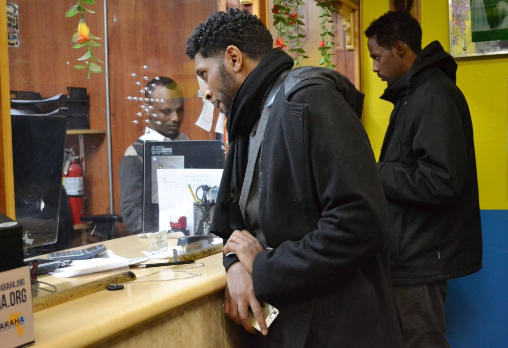Customer Ali Adam gets assistance at Kaah Express, a hawala in Cedar-Riverside, on Tuesday evening. Hawalas serve as middle men between money senders in the U.S. and recipients in countries like Somalia.