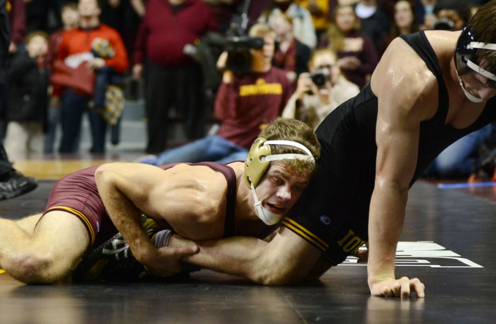 Senior Dylan Ness wrestles during his match in the Williams Arena on Jan. 30 against the Iowa Hawkeyes.
