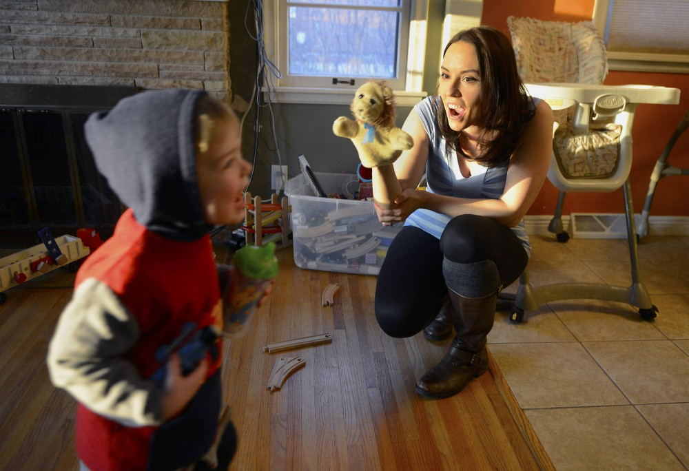 University instructor and doctoral candidate Ruth DeFoster plays with her two-year-old son Anthony in the living room of their home in St. Paul on Thursday. DeFoster has faced criticism from some her graduate school peers for her decision to have children while attending school.