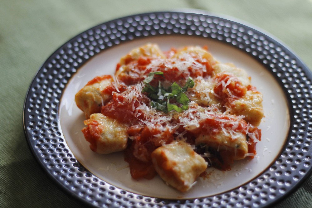 A fresh plate of ricotta gnocchi topped with rustic homemade tomato sauce.
