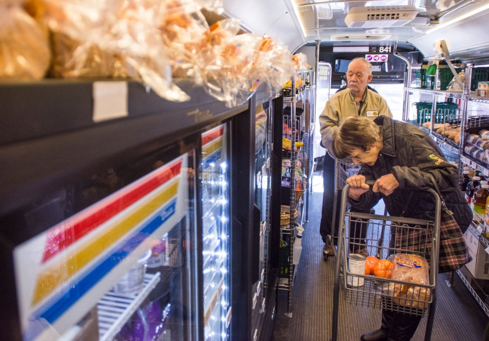 Market customers Saverna Chapman and Ron Murray shop for groceries on the Twin Cities Mobile Market bus in St. Paul on Saturday. The bus acts as an inexpensive grocery store for neighborhoods that don't have access to local healthy foods at a low cost.
