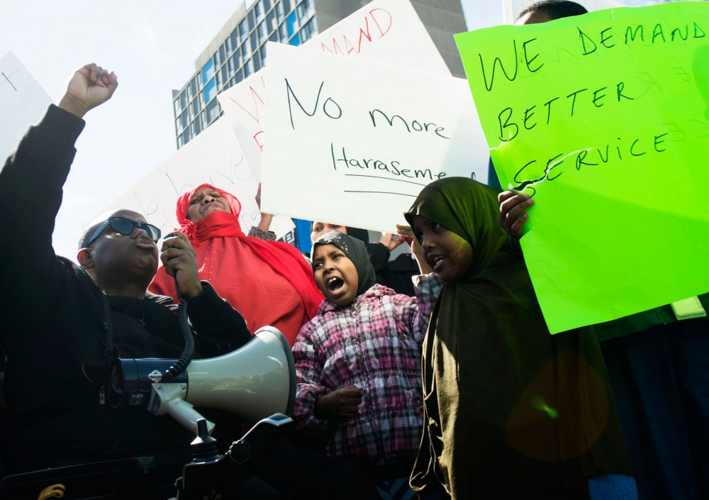 Abdi Huk, left, and tenant Samira Sammy, center, lead the crowd in protest chants outside Riverside Plaza on Friday afternoon. About 100 people gathered to protest building management.