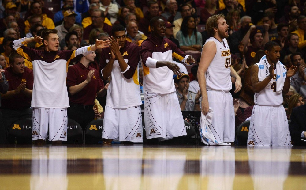 The Minnesota bench reacts after guard Andre Hollins scored his third three-pointer in the first half against Penn State at Williams Arena on Sunday.