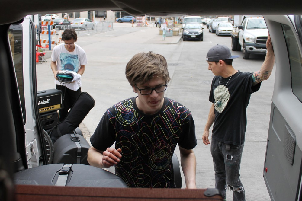 Donovan Wolfington band members Mike Saladis, Chris Lanthier, and their friend Chance, load gear onto their tour van after performing at a Top Shelf show in Austin, Texas on Thursday, March 19th.