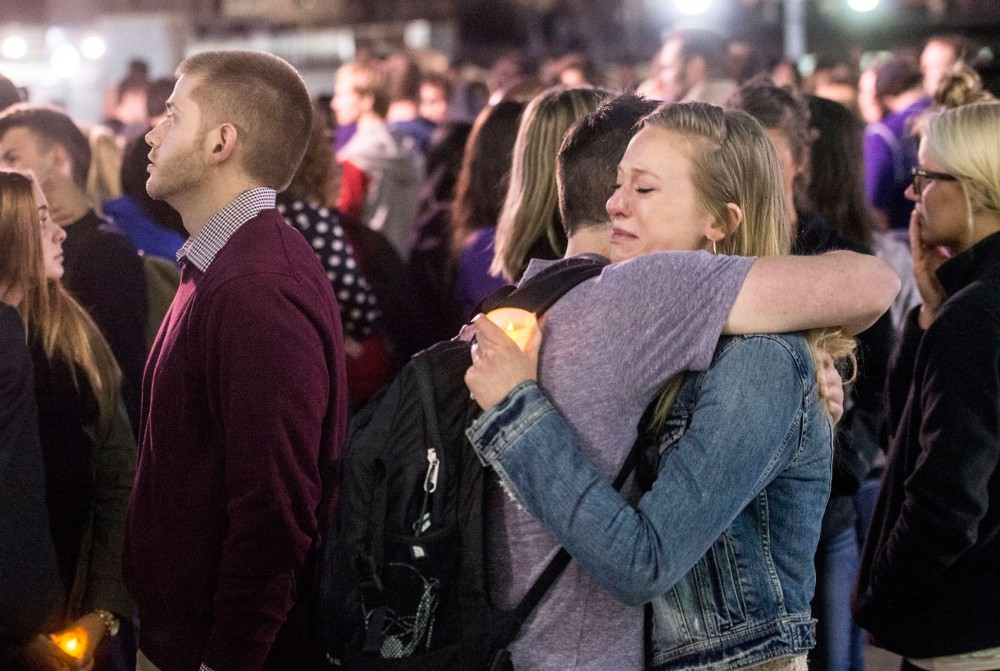 A friend of Jennifer Houle holds a candle and receives a hug at the candlelight vigil outside of Coffman Memorial Union on Tuesday. The vigil was held to honor Houle, who went missing March 27.