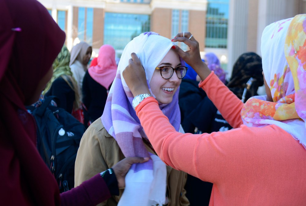 Junior Anastasia Press (center) smiles as Freshman Megan Abdirahman (right) helps her put on a hijab for