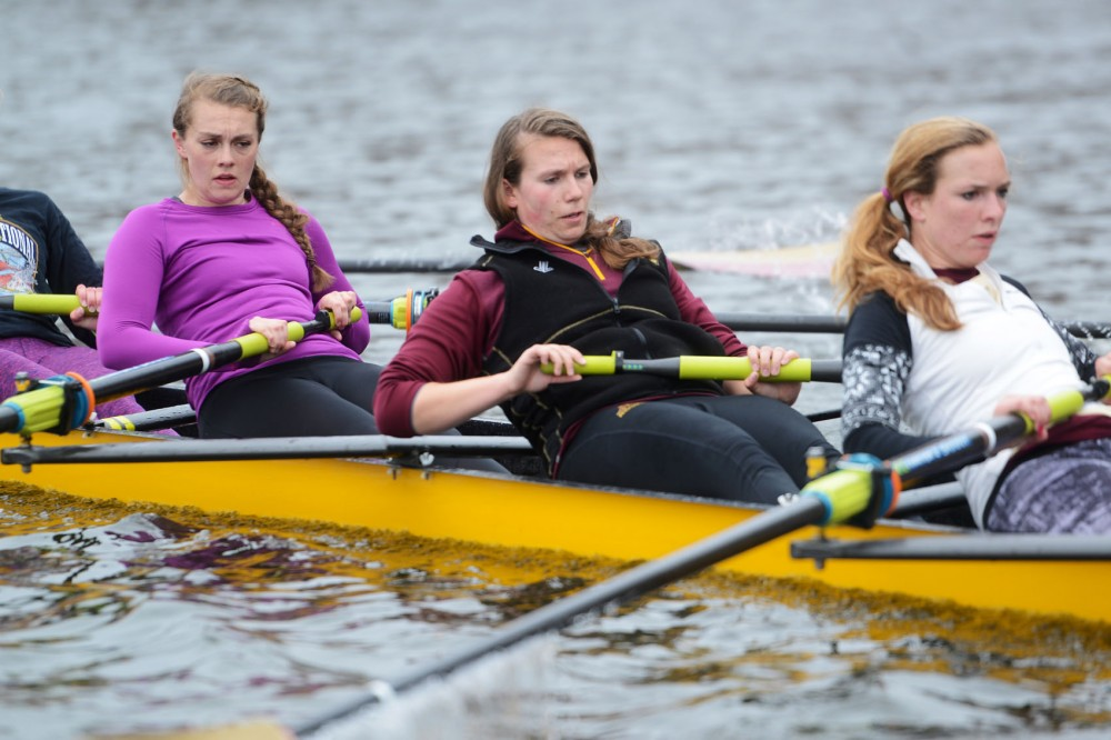 Senior Lynn Hodnett (second from right) practices with the rowing team on Monday in the Mississippi River.