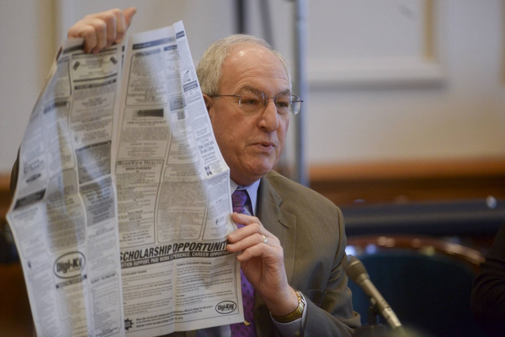 Sen. LeRoy Stumpf, DFL-Plummer, holds up the classified section of a local newspaper to illustrate workforce shortages in Minnesota at the state Capitol on Tuesday. Stumpf authored a bill this session that would offer free tuition to certain high school students entering community and technical colleges in the state.