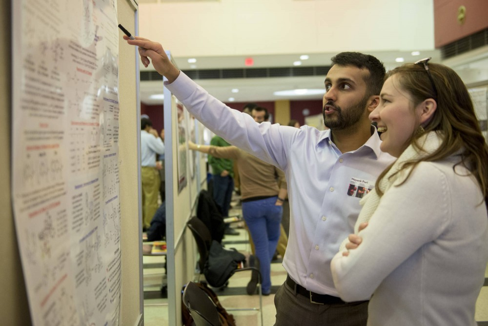 Mayank Puri presents his chemistry doctoral dissertation to Robin Voreis on Tuesday afternoon at Coffman Union during the 2015 Doctoral Research Showcase.