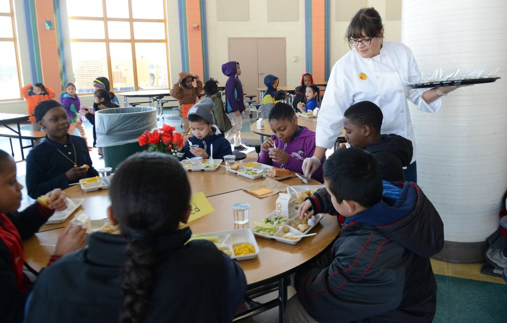 Chef Erica Strait of Foxy Falafel serves kids as they partake in a taste test through the True Food Chef Council at Cityview Community School in Minneapolis on March 6. The Council partners with Minneapolis Public Schools for these taste tests to help come up with possible improvements in Minneapolis Public School lunch menus.