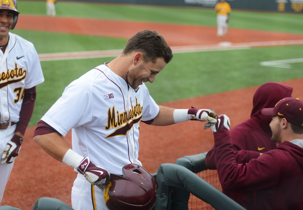 Redshirt senior Michael Handel celebrates with teammates after hitting a home run at Siebert Field on Wednesday afternoon against the Carleton College Knights.
