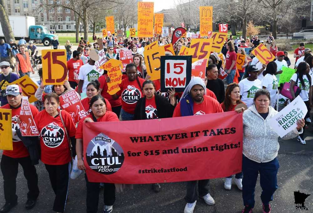 Hundreds of people march down Pleasant Street SE towards McDonald's in Dinkytown in a protest to raise Minneapolis' minimum wage to $15 per hour on Wednesday.
