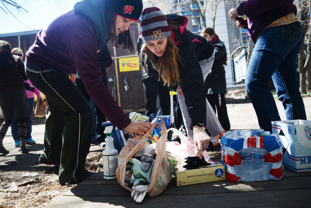 St. Catherine University first-year physical therapy students Taylor Hutchins, left, and Brittany Lehner grab gloves before picking up garbage and cleaning graffiti near Cedar Avenue in Minneapolis on Wednesday. The event was one of many the Cedar-Riverside Community Collaboration Group planned this week for Earth Day.