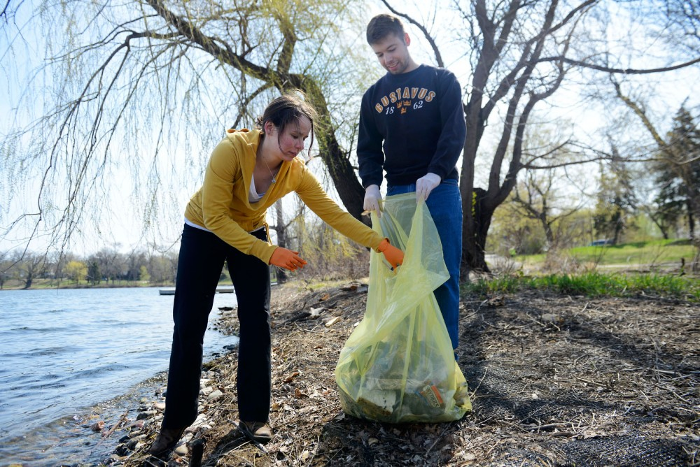 Graduate students Megan Cross and Grant Cooper pick up trash for Minneapolis Parks and Recreation Board's Earth Day cleanup at Lake of the Isles on Saturday. Members of the student group Natural Resources Association of Graduate Students decided to participate in the event to support Earth Day.
