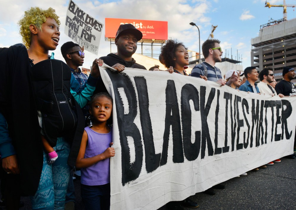 Jackquline Gates, left, and her daughter, Samiyah, sing as they march along Washington Avenue in downtown Minneapolis on Wednesday evening.