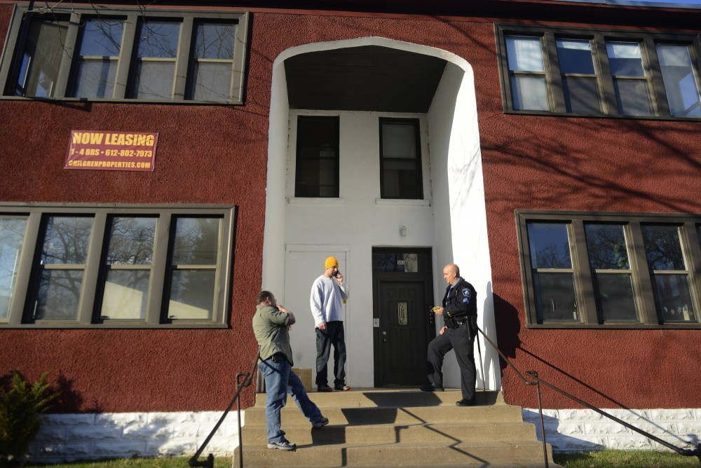 Police officers stand on the steps of a multi-tenant housing unit on the corner of Fifth Avenue Southeast and Sixth Street Southeast on Friday. Residents were evacuated after unknown chemicals were found in the building on April 10, 2015.