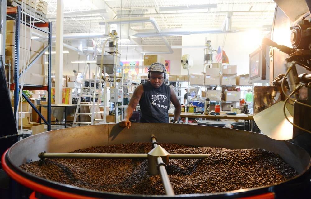 Ivoire Foreman oversees the roasting process of coffee beans at the Peace Coffee Roastery on Friday. Peace Coffee sells organic, fair-trade coffee in its coffee shops as well as many retail locations.