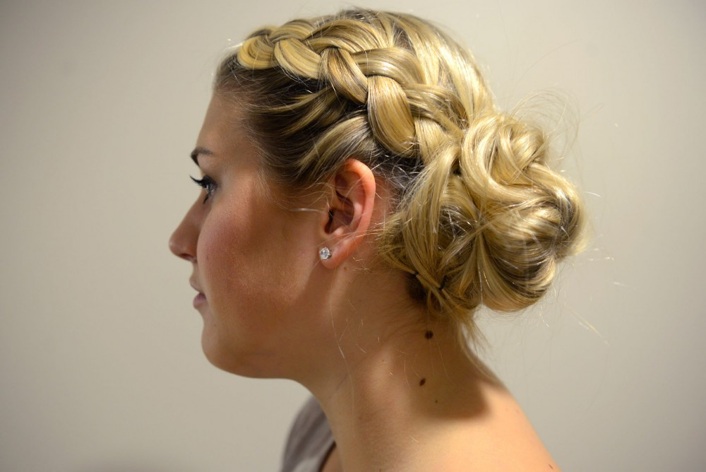 Freshman Liz Carver models a french braided messy bun at 17th Avenue Residence Hall on Friday afternoon. A french braided messy bun is a simple heatless up-do for summer.
