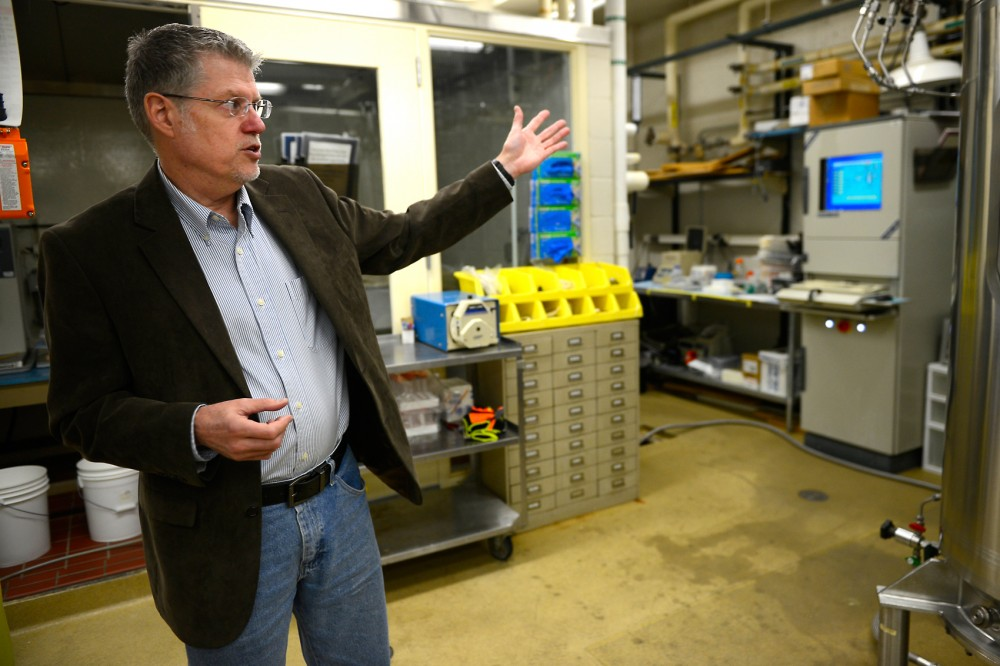 Professor Larry Wackett explains the usage of large-scale laboratory equipment on Friday. University labs have become more commercialized, bridging the gap between research and real-world applications.