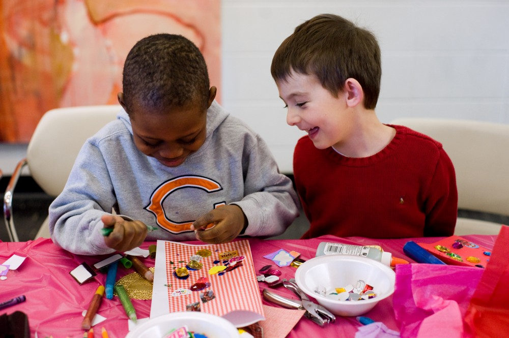 Five-year-old Jay McCurtis, left, squeezes green glitter glue on his valentine while his friend and classmate Jesse O'Leary, 6, laughs next to him. The two were making valentine cards Saturday morning at Kresge Art Center for the You Gotta Have HeART! Creative Kids event. Georgia Rhodes/The State News