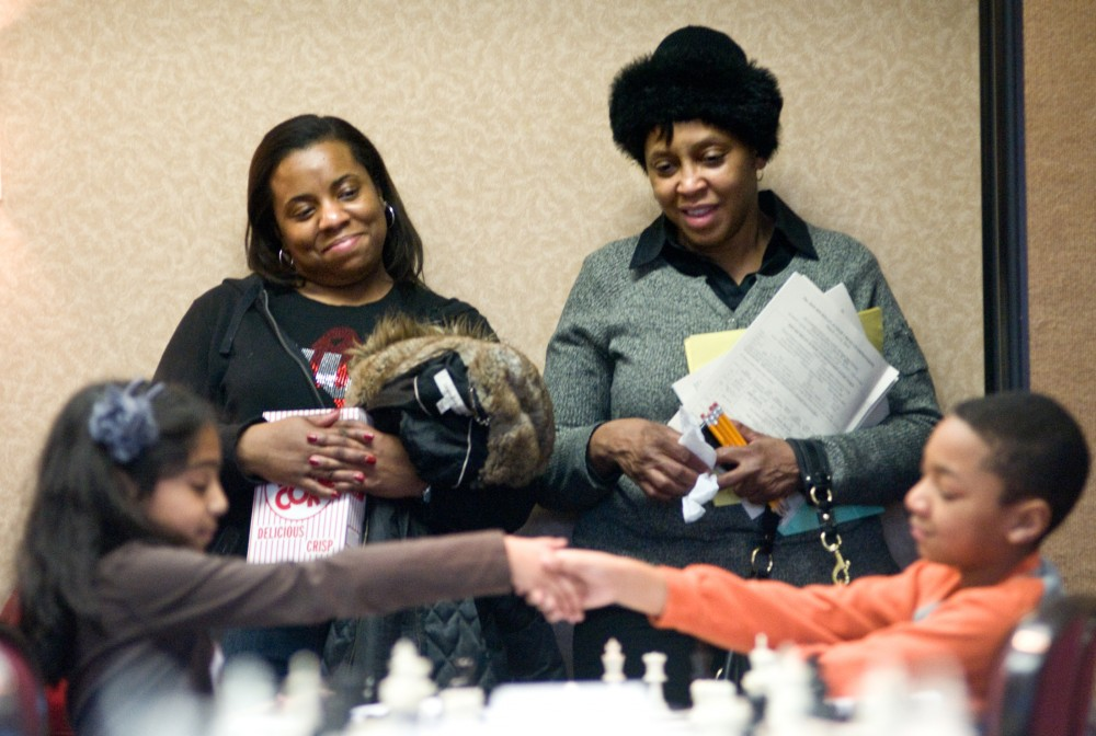 Detroit residents Tracy Walker and Edith Love smile as Bates Academy student Jordan Walker, 9, shakes his opponent's hand, Northville Ridgewood Elementary student Rachna Munagala, 9, after she defeated him in a chess match. The State Elementary Team Chess Championship was held at the Union on Saturday afternoon. Josh Radtke/The State News