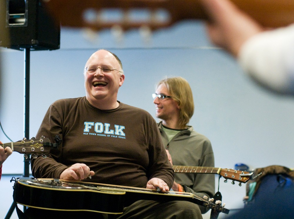 Chicago resident Pat Murphy, left, and doctoral student in teacher education Mark Kissling have a laugh between songs during a folk music workshop Saturday at the Mid-Winter Singing Festival held at the Hannah Community Center, 819 Abbott Road. Kat Petersen/The State News
