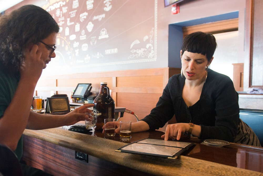 Bartender Vanessa Smith sells a growler of beer to a customer at Town Hall Brewery on Monday. On June 5 the city council will vote on possible changes that would allow the sale of growlers on Sundays at breweries and taprooms, as well as changing the time for Sunday sales from 10 a.m. to 8 a.m.
