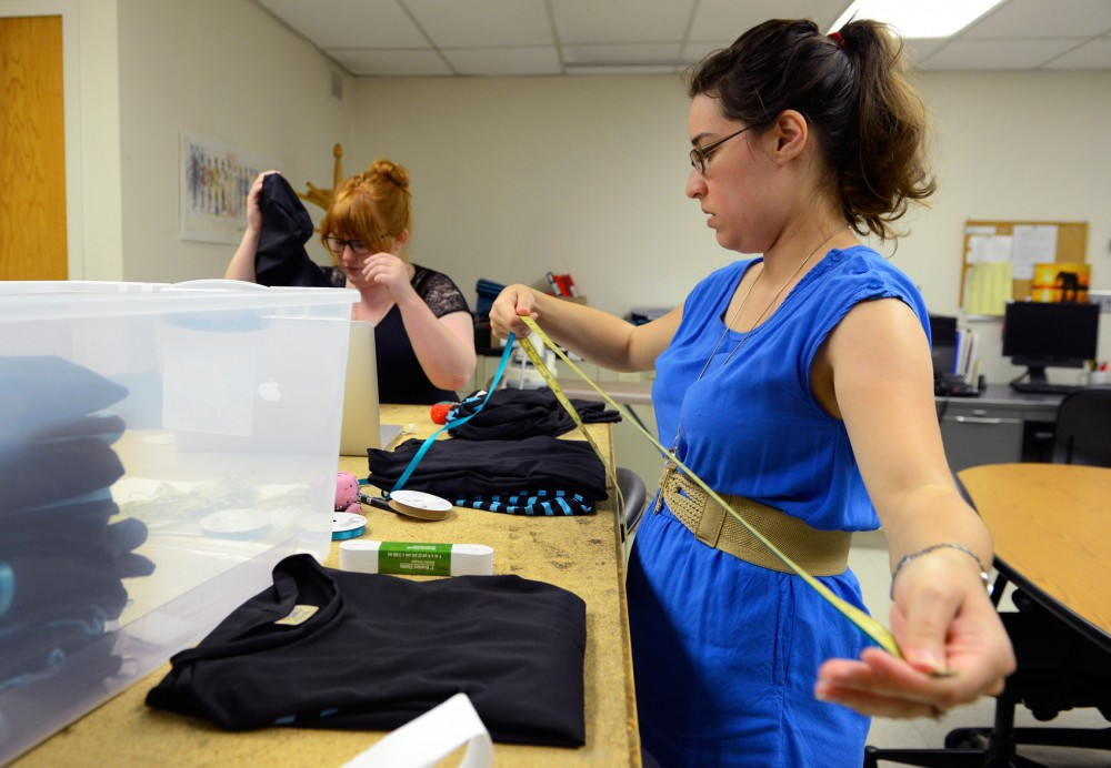 Graduate design students Robin Carufel and Kira Erickson put the finishing touches on dresses designed for activewear in McNeal Hall on Monday. Tucker Center researchers worked with College of Design students to create a line of culturally appropriate activewear that East-African middle school girls will model at a fashion show on June 10.
