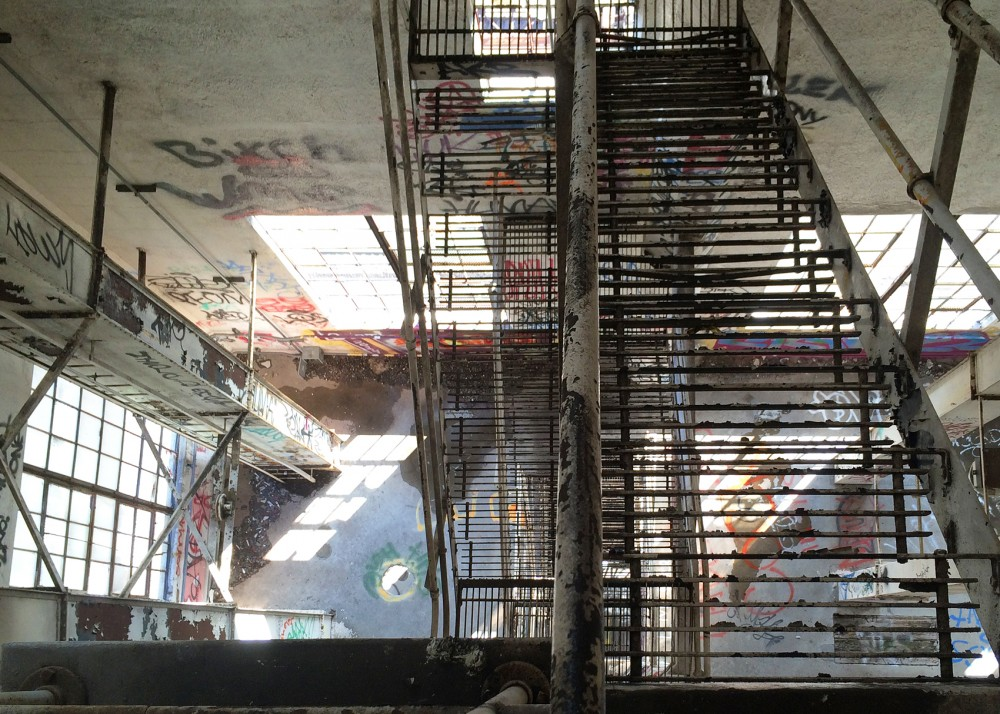 As seen from above, a series of rusted metal stairs sit inside of the empty and graffiti-filled interior of the abandoned Bunge Grain Elevator in Southeast Como on May 25, 2015.